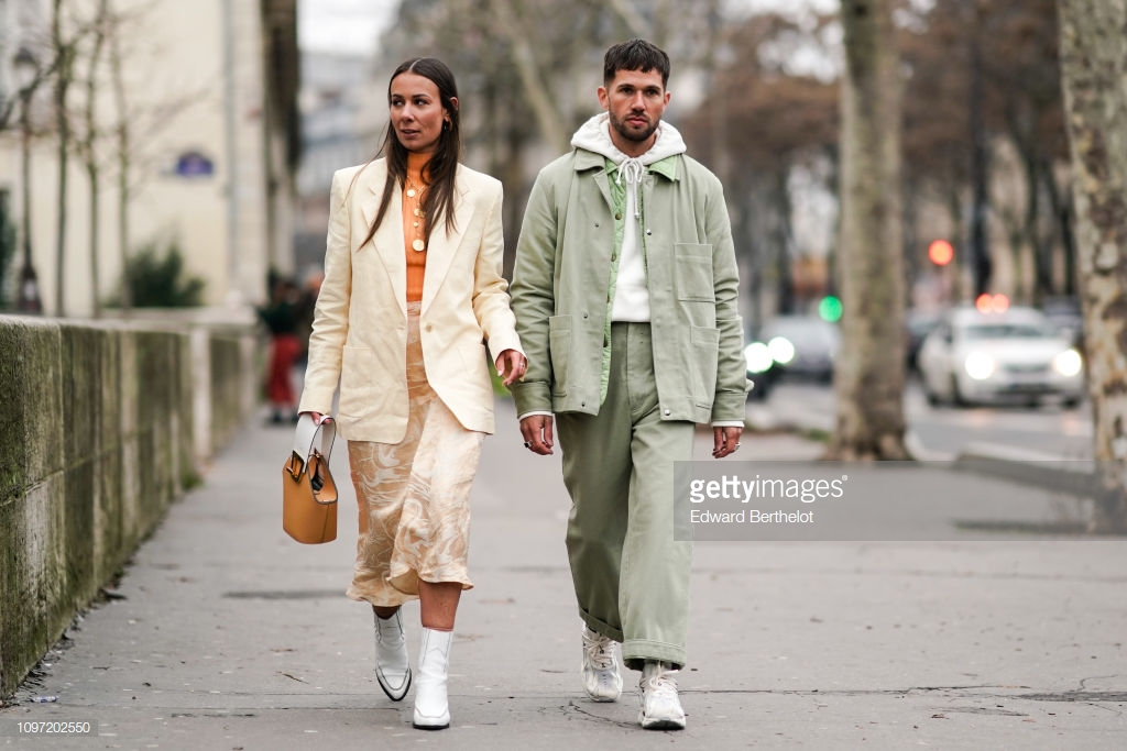 PARIS, FRANCE - JANUARY 20: Alice Barbier wears a white blazer jacket, cropped pants, white boots, a brown bag ; Jean-Sebastien Rocques wears a green jacket, a white hoodie sweater, green pants, sneakers, outside Acne, during Paris Fashion Week - Menswear F/W 2019-2020, on January 20, 2019 in Paris, France. (Photo by Edward Berthelot/Getty Images)